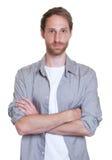 Tipo tedesco alla moda con la barba e armi attraversate in camicia grigia Fotografie Stock