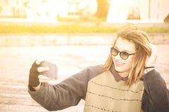 Tipo teenager di giovane rasta bello con il selfie degli occhiali da sole nella città Immagine Stock Libera da Diritti