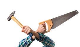 Tipo in una camicia rossa del plaid che tiene una sega di legno e un martello Immagine Stock