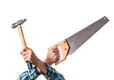 Tipo in una camicia rossa del plaid che tiene una sega di legno e un martello, crosse Fotografie Stock