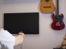 Tipo, uomo, canali del commutatore dei pantaloni a vita bassa sulla TV, nella progettazione della sala con una chitarra, nessun s Fotografie Stock Libere da Diritti