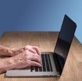 Tipos adultos mayores del tacto del hombre en el ordenador portátil Imagen de archivo