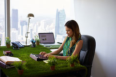 Tipos correo electrónico de la mujer del ecologista con la tableta en el escritorio de oficina Imagen de archivo