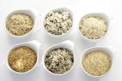 Tipos de arroz em umas bacias, cru e cozinhado Imagens de Stock