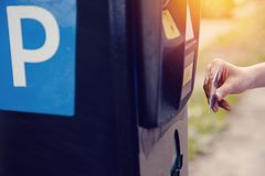 Tipos de la muchacha el texto con sus manos para hacer el boleto para el aparcamiento y el pago de la máquina que parquean para e foto de archivo