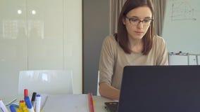 Tipos de la muchacha en el ordenador portátil en la oficina