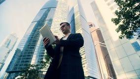 Tipos del hombre de negocios en una tableta en el fondo de los rascacielos, visión inferior