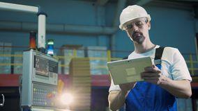 Tipos del trabajador de planta en una tableta, colocándose en un cuarto de la instalación almacen de metraje de vídeo