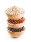 Tipos diferentes de arroz no bacias de madeira isoladas no branco Fotografia de Stock Royalty Free