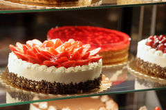 Tipos diferentes de bolos na exposição de vidro da loja de pastelaria Imagens de Stock