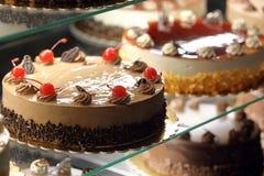 Tipos diferentes de bolos na exposição de vidro da loja de pastelaria Foto de Stock