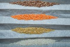 Tipos diferentes de cereais e de leguminosa nos grãos-de-bico de papel do pergaminho, lentilhas vermelhas, trigo mourisco, arroz imagens de stock