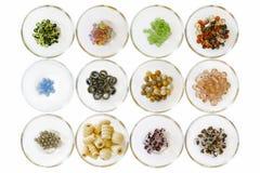 Tipos diferentes de grânulos; no branco em umas bacias de vidro pequenas fotografia de stock