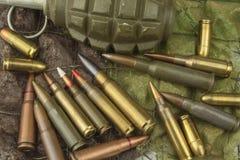 Tipos diferentes de munição em um fundo da camuflagem Preparação para a guerra Fotografia de Stock Royalty Free