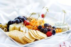 Tipos diferentes de petiscos do vinho: queijos, biscoitos, frutos e azeitonas na tabela branca Imagens de Stock