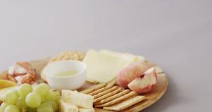 Tipos diferentes de queijo, de biscoitos friáveis, de frutos e de molho na placa de madeira filme