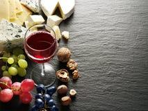 Tipos diferentes de queijos com vidro e frutos de vinho Fotos de Stock Royalty Free