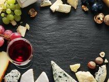 Tipos diferentes de queijos com vidro e frutos de vinho Foto de Stock