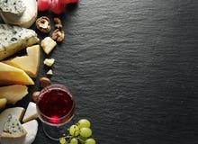 Tipos diferentes de queijos com vidro e frutos de vinho Imagem de Stock Royalty Free
