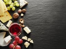 Tipos diferentes de queijos com vidro e frutos de vinho Imagens de Stock