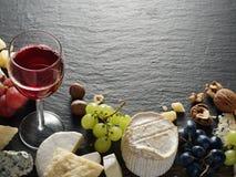 Tipos diferentes de queijos com vidro e frutos de vinho Fotografia de Stock