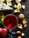 Tipos diferentes de queijos com vidro e frutos de vinho Imagens de Stock Royalty Free
