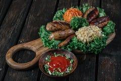 Tipos diferentes de salsichas fritadas grelhadas com couve cozido e chucrute Imagem de Stock