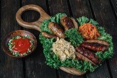 Tipos diferentes de salsichas fritadas grelhadas com couve cozido e chucrute Fotos de Stock