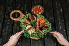 Tipos diferentes de salsichas fritadas grelhadas com couve cozido e chucrute Foto de Stock