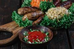 Tipos diferentes de salsichas fritadas grelhadas com couve cozido e chucrute Foto de Stock Royalty Free