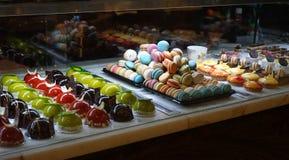 Tipos diferentes de sobremesas do bolo na exposição de vidro da loja de pastelaria Fotos de Stock