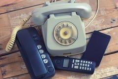 Tipos diferentes de telefones na placa de madeira Fotografia de Stock
