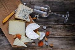 Tipos diferentes de vidro do queijo e de vinho em uma placa de madeira Imagem de Stock