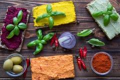 Tipos diferentes do hummus, da paprika, do abacate, do caril e das beterrabas na tabela marrom imagens de stock
