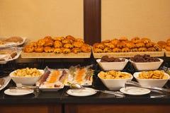 Tipos diferentes dos doces e do produtos de forno no banquete foto de stock
