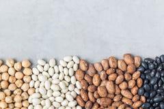Tipos diferentes dos feijões: o preto, o pinto, o branco e os grãos-de-bico, em um fundo concreto, copiam o espaço, horizontal Foto de Stock