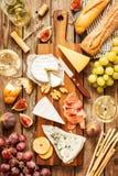 Tipos diferentes dos queijos, do vinho, do baguette, dos frutos e dos petiscos Imagem de Stock