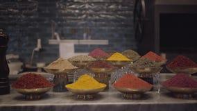 Tipos diferentes dos temperos no contador da loja em umas bacias do metal Variedade de especiarias e de ervas na tabela filme