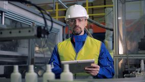 Tipos do homem em uma tabuleta ao verificar o equipamento da fábrica, produção automatizada vídeos de arquivo