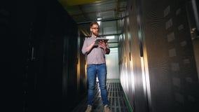 Tipos do homem em uma tabuleta, verificando a sala do servidor equipmnent video estoque