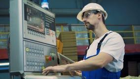 Tipos masculinos do trabalhador em uma máquina da fábrica, equipamento moderno vídeos de arquivo