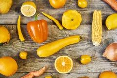 Tipos sortidos de frutas e legumes amarelas no backgro de madeira imagem de stock royalty free
