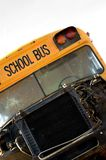 Tipped School Bus. Isolated wrecked school bus with cracked windshield and engine exposed Stock Photography