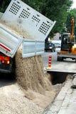 Перевезите tipper на грузовиках во время опорожнять дороги гравия во время e Стоковые Фотографии RF