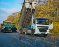 Tipper dump truck unload fresh asphalt at the road. For renewal. heavy machines making new highway at countryside. wide fall autumn outdoor shot stock images