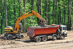 Tipper truck loaded by an excavator. Yellow excavator excavate on site and loaded a orange tipper truck Stock Photography