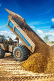 Tipper unloadding sand from scoop Royalty Free Stock Photos