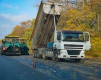 Tipper usypu ciężarówka rozładowywa świeżego asfalt przy drogą obrazy stock