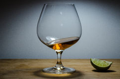 Tipple Time. Brandy glass on a wooden board with a lime Royalty Free Stock Photos