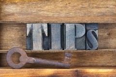 Tips key tray. Tips word made from wooden letterpress type inside tray with ancient rusty key Royalty Free Stock Images